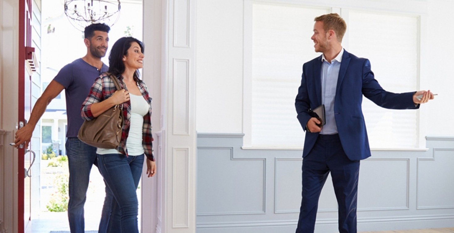 Realtor walking couple in home